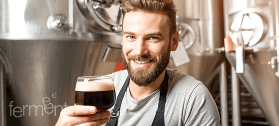 Craft beer brewer in front of beer brewing equipment with a dark beer
